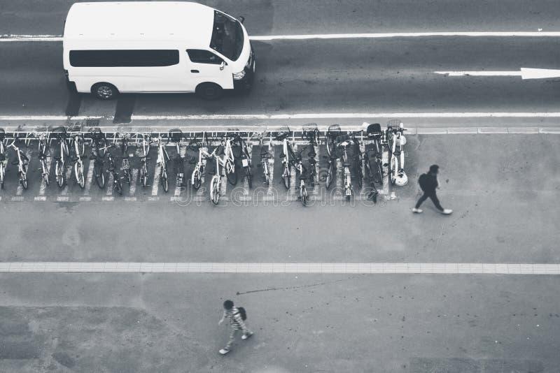 Abstrakt svartvit bild av raden för flyg- sikt av cyklar som parkeras på parkeringsplatsen och bilen som kör på vägen arkivfoton