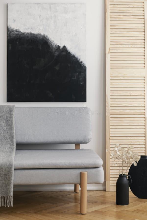 Abstrakt svartvit målning på den vita väggen av naturlig vardagsrum som är inre med den gråa stilfulla soffan arkivbilder