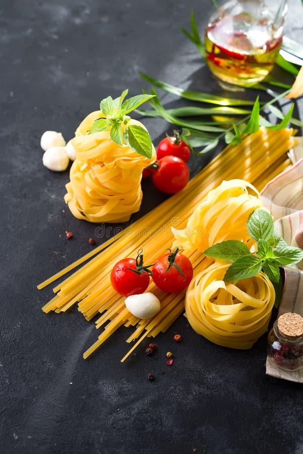 abstrakt textur för bakgrundsmatpasta Flera typer av torr pasta med grönsaker och örter på en mörk stentabell Fritt avstånd för t fotografering för bildbyråer
