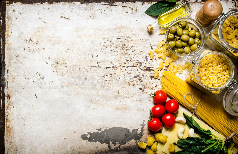 abstrakt textur för bakgrundsmatpasta Mycket olika pasta, oliv, tomater, olja och örter arkivfoton