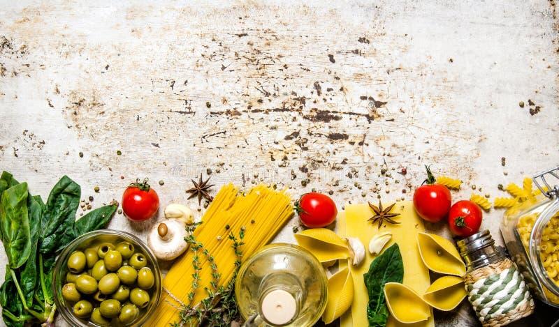 abstrakt textur för bakgrundsmatpasta Mycket olika pasta, oliv, tomater, olja och örter royaltyfria bilder