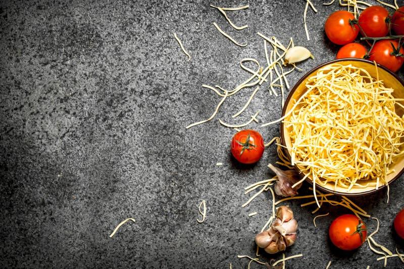 abstrakt textur för bakgrundsmatpasta Nudlar med tomater och vitlök royaltyfri bild