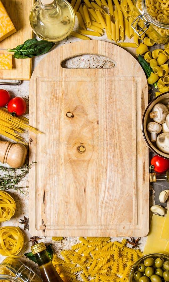 abstrakt textur för bakgrundsmatpasta Torr pasta med grönsaker, champinjoner, ost och örter med en tom platta arkivfoto