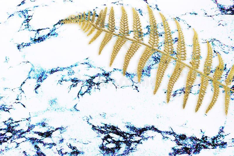 Abstrakt textur med bladet för den guld- ormbunken, gömma i handflatan på vitmarmorbakgrund för designmodellkonstverk, modernt be royaltyfri foto