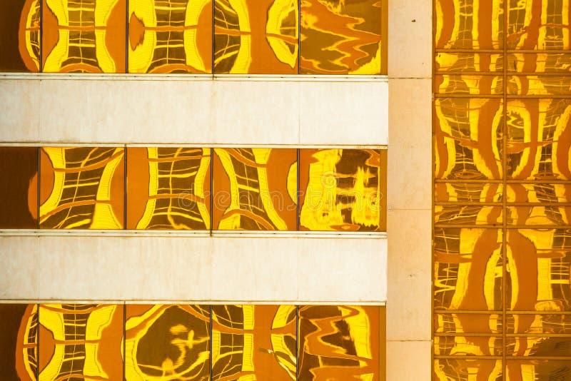 Abstrakt tworzył Złotymi żółtymi odbiciami na nowożytnym budynku fotografia stock