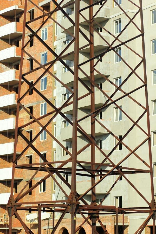 Abstrakt vertikal industriell bakgrund av flervånings- byggnad för tegelsten under konstruktion bak nära övre kraftledningpylonto royaltyfri fotografi