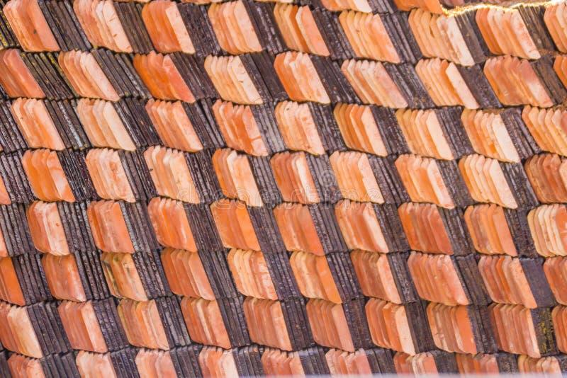Abstrakt wypiętrza nowe gliniane ceramiczne płytki zakrywać dach Buddyjska świątynia i pakuje Sterta nowe pomarańczowe dachowe pł zdjęcie royalty free