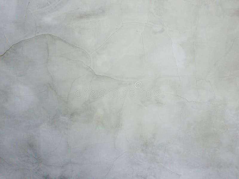 Abstrakt yttersida av den släta gråa murbrukväggen med sprickor och skrapor Gammal grungy riden ut konstruktionsstruktur som är s royaltyfri bild