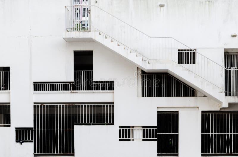 Abstrakt yttre arkitektonisk bakgrund - skyddsgallerfönster av olika former och format på den vita betongväggen royaltyfria foton