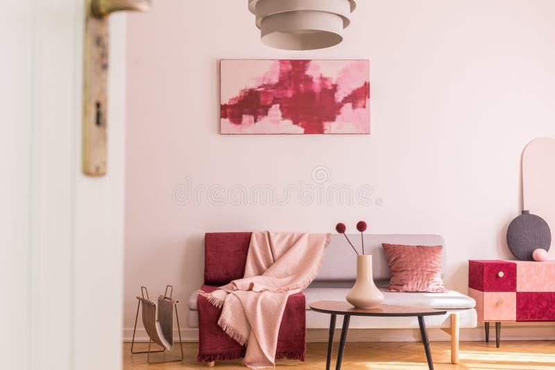 Abstrakta burgundy och pastellfärgad rosa målning på den tomma vita väggen av moderiktig vardagsrum som är inre med den gråa soff arkivbilder