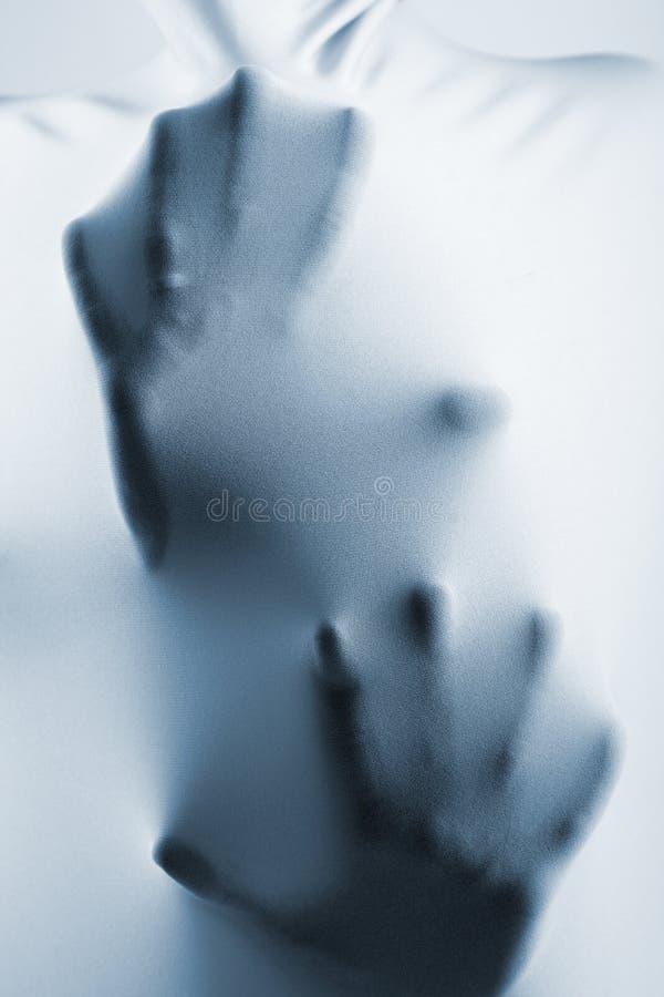 Abstrakta händer, mänsklig arm inom tyg, tonad blått arkivfoto