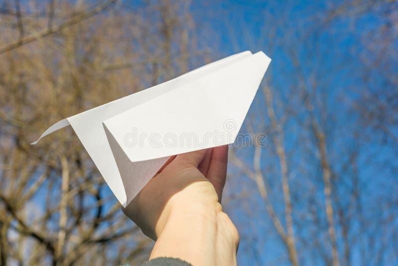 Abstrakta papieru samolot w ręce, niebieskie niebo, wiosen drzew słońca tło fotografia royalty free