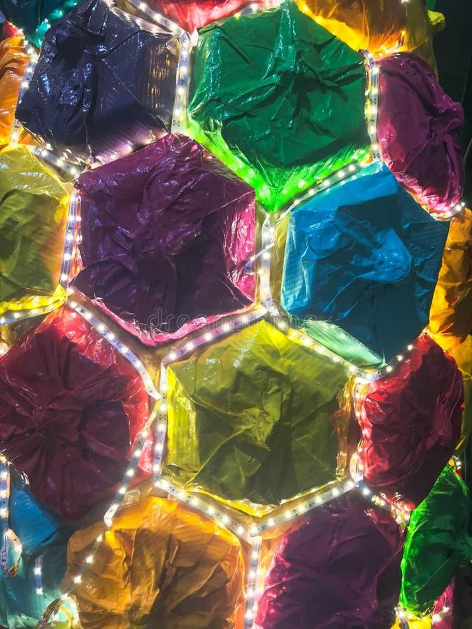 Abstrakta plast- konstgjorda mångfärgade skinande glödande LEDDE gladlynta härliga glade sexhörniga celler för ferie Bakgrund tex arkivfoto