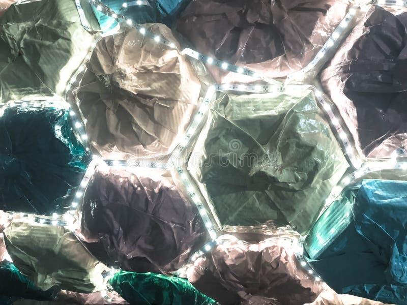 Abstrakta plast- konstgjorda mångfärgade skinande glödande LEDDE gladlynta härliga glade sexhörniga celler för ferie Bakgrund tex royaltyfri fotografi