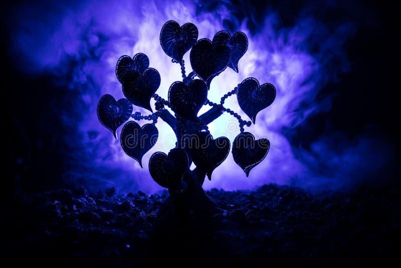 Abstrakta pole z drzewem i serca na nim za ciemnym mgłowym stonowanym niebem Miłości drzewo sen valentine pojęcia tło obrazy royalty free
