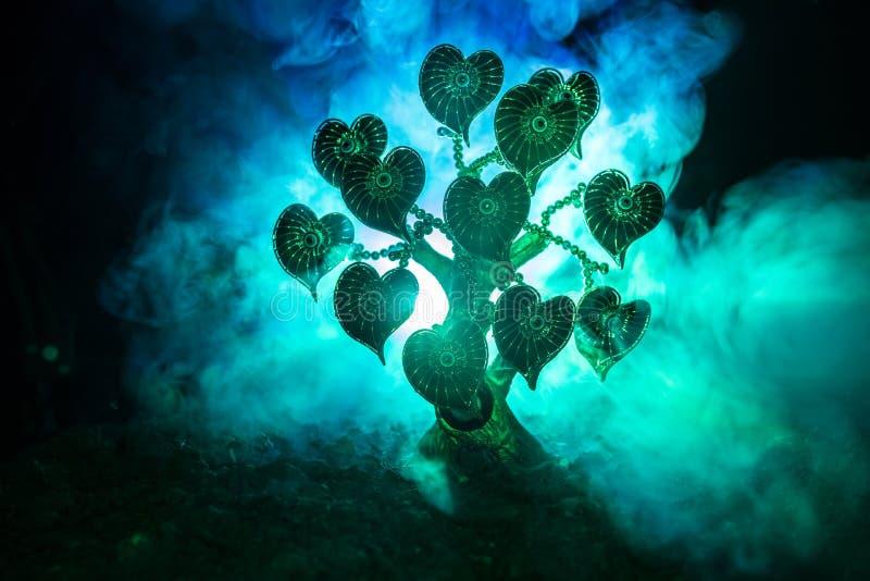 Abstrakta pole z drzewem i serca na nim za ciemnym mgłowym stonowanym niebem Miłości drzewo sen valentine pojęcia tło fotografia stock