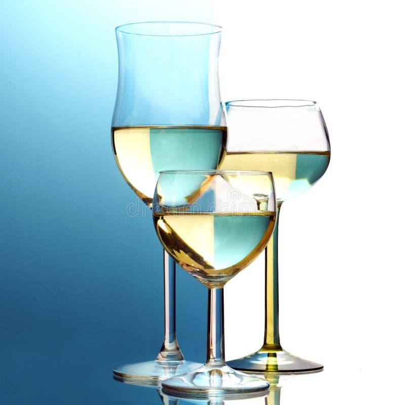 Abstrakta vinexponeringsglas, halva blått för bakgrund, halv vit royaltyfri bild