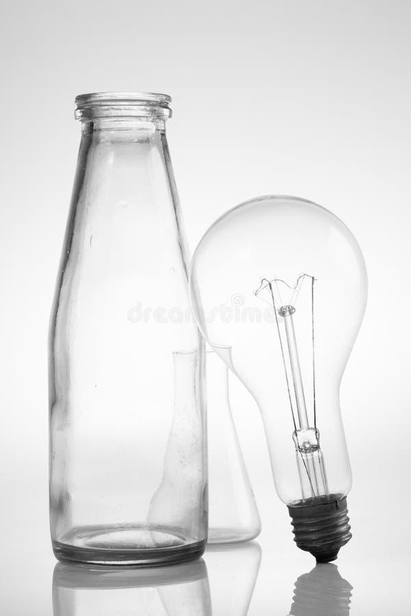 Abstrakta wciąż życie z jasnymi szklanymi rocznik butelkami i elektryczną lampą fotografia stock
