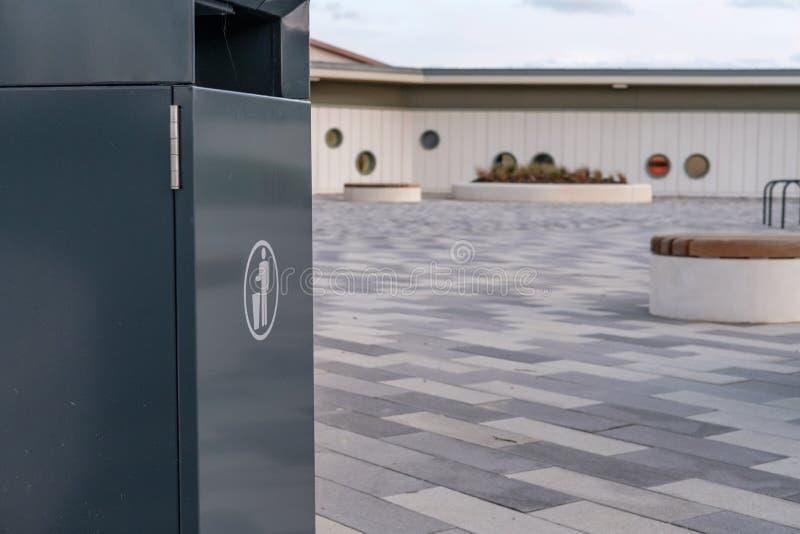 Abstrakte Ansicht, die einen Metallsänftenbehälter zusammen mit einem eben errichteten Einkaufszentrum und einer Schule zeigt lizenzfreie stockfotos