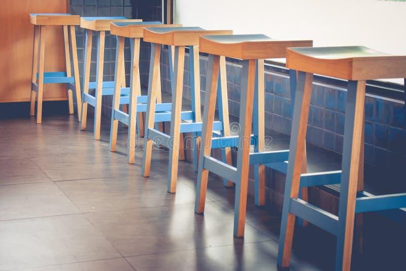 Abstrakte Architekturreihe von leeren Weinleseholzstühlen verzieren im Kaffeecafé stockfotografie