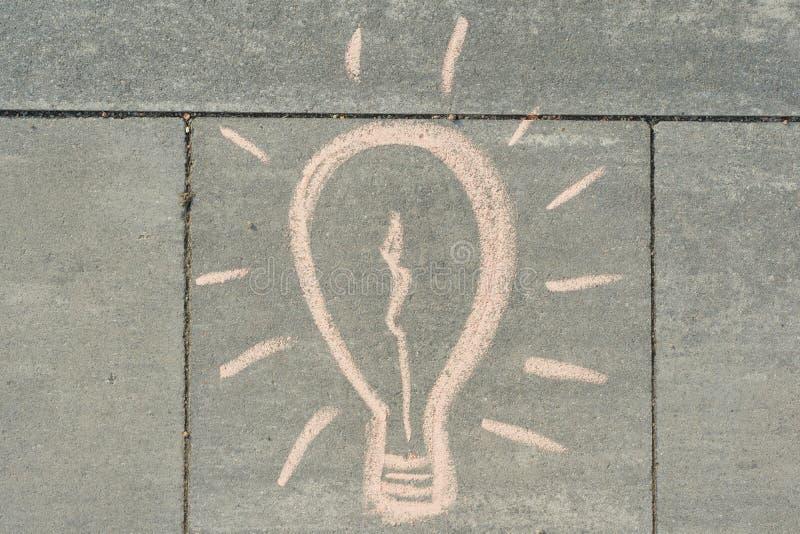 Abstrakte Bildzeichnung der Glühlampe geschrieben auf grauen Bürgersteig stockfotografie