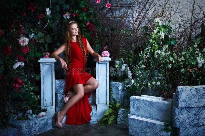 Abstrakte Fantasiehintergründe mit magischem Buch Schöne Prinzessin im roten Kleid, das in einem mystischen Garten sitzt lizenzfreies stockbild