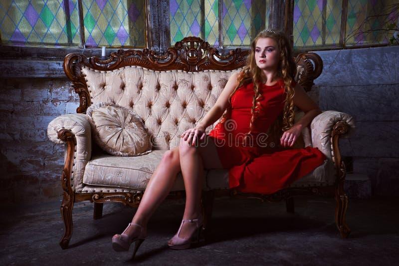 Abstrakte Fantasiehintergründe mit magischem Buch Schöne Prinzessin im roten Kleid, das in einem mystischen Garten sitzt stockfotografie