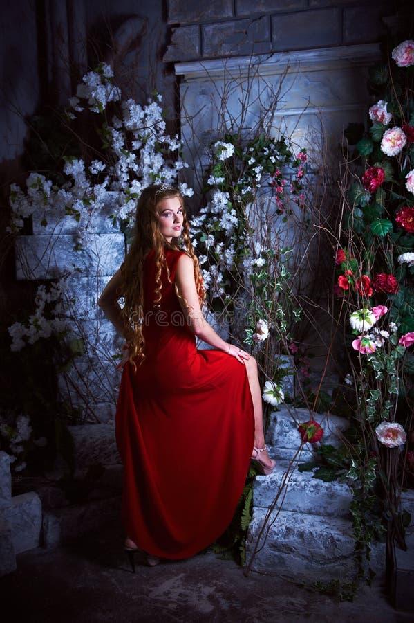Abstrakte Fantasiehintergründe mit magischem Buch Schöne Prinzessin im roten Kleid, das in einem mystischen Garten sitzt stockbilder