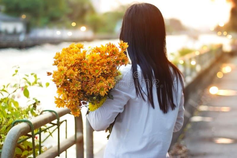 Abstrakte Frau mit Blumenstrauß blüht vibrierendes in den Händen auf Straße und Kanal lizenzfreie stockfotos