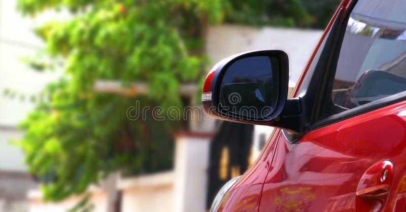 Abstrakte Nahaufnahme des Seitenrückspiegels auf einem roten modernen Auto lizenzfreie stockbilder