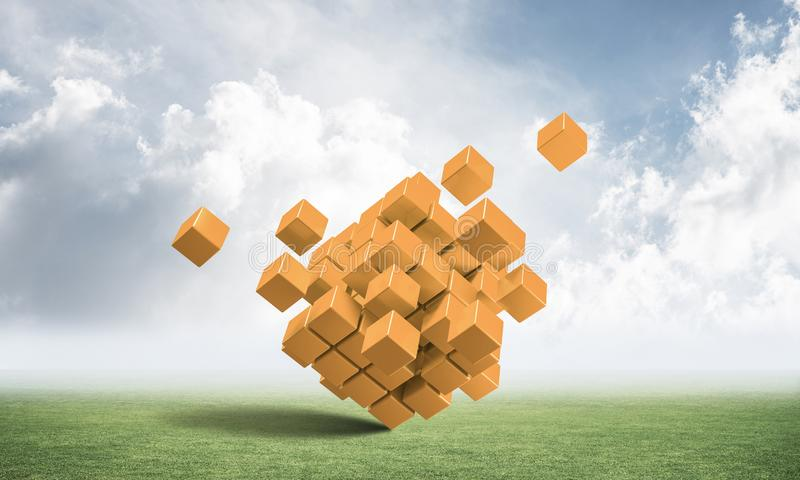 Abstrakte orange Würfel auf grüner Wiese lizenzfreie stockbilder