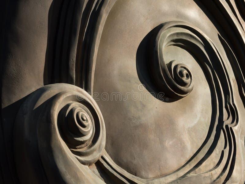 Abstrakte Spiralen an der Rückseite eines Bronzemonuments lizenzfreies stockbild