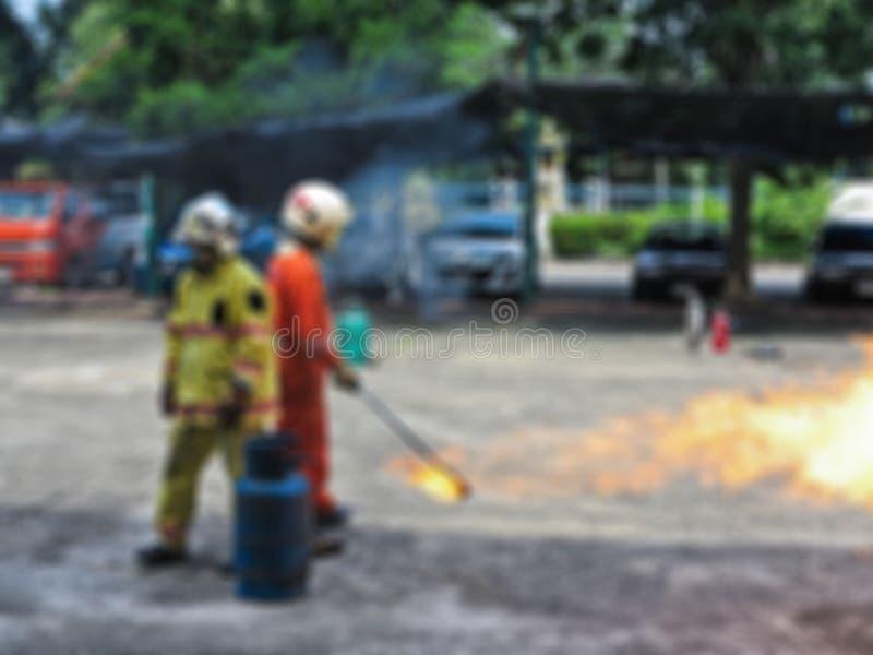 Abstrakte Unschärfeleute, die wie man Feuer im Feuerbekämpfungs-Ausbildungskurs üben, stoppt Sicherheit erste lizenzfreie stockfotos