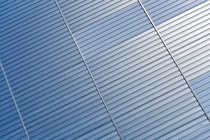 Abstrakter Architekturhintergrund von der modernen Gebäudefassade mit den blauen und silbernen Linien - Bild stockfotografie