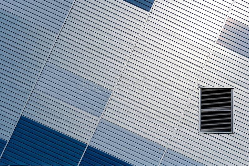 Abstrakter Architekturhintergrund von der modernen Geb?udefassade mit den blauen und silbernen Linien - Bild stockfotografie