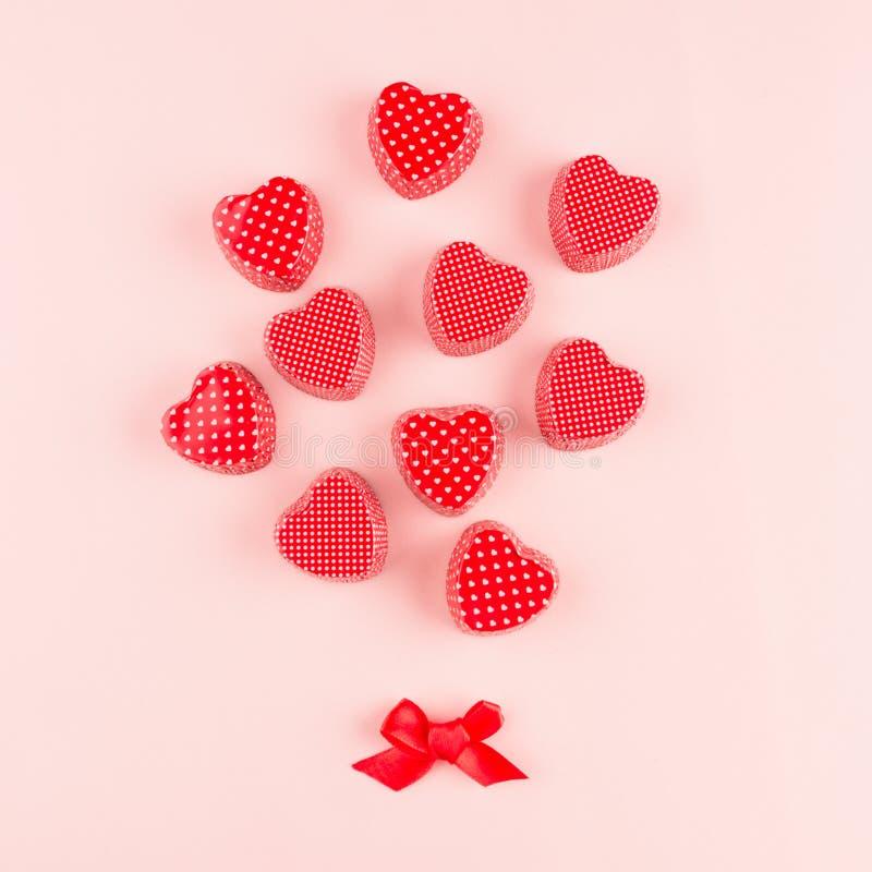 Abstrakter Blumenstrauß von roten Herzen auf weichem rosa Farbhintergrund, Valentinsgrußkarte Valentine Day-Hintergrund stockbild
