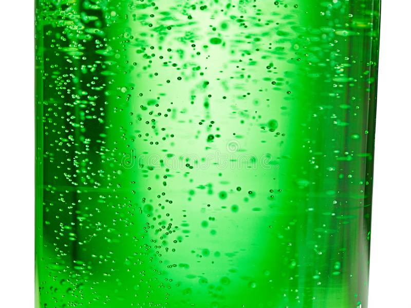 Abstrakter Hintergrund: Blase des Sodas des funkelnden Wassers auf der grünen Glasflasche mit Steigungslicht stockbild