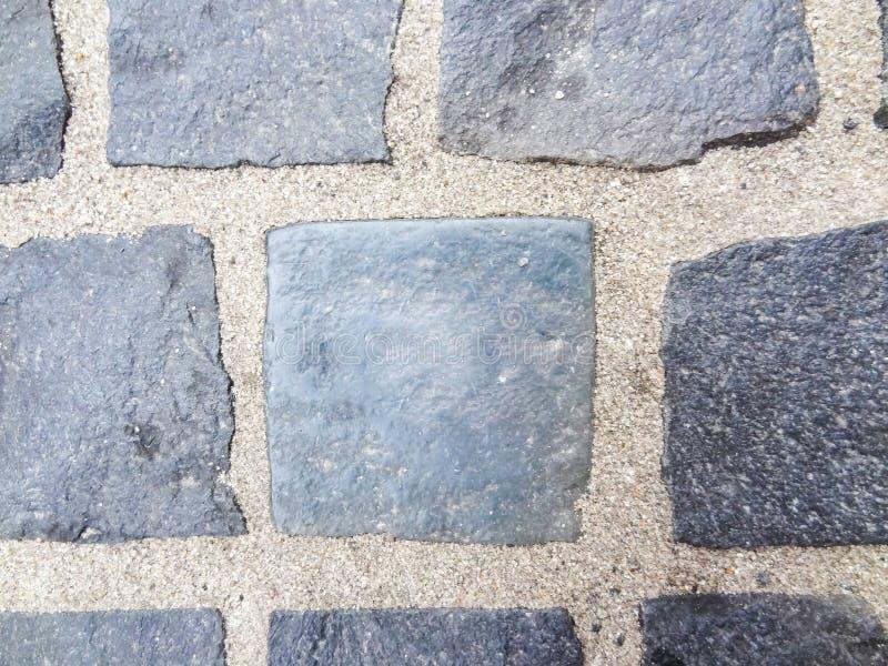 Abstrakter Hintergrund des alten Abschlusses der Kopfsteinpflasterung oben Steinbeschaffenheit der Pflasterung Granit, der Pflast stockfoto