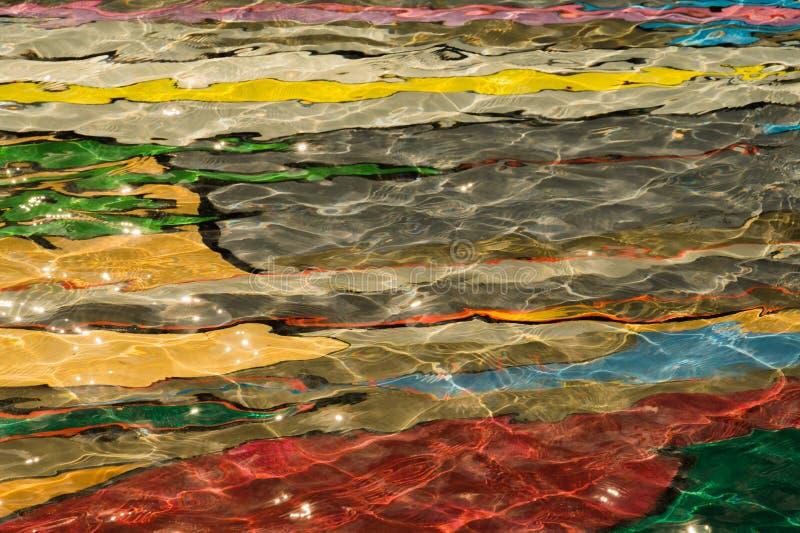 abstrakter Hintergrund des bunten Poolwassers farbige Unterseite des Swimmingpools mit geplätschertem Wasser lizenzfreie stockfotos