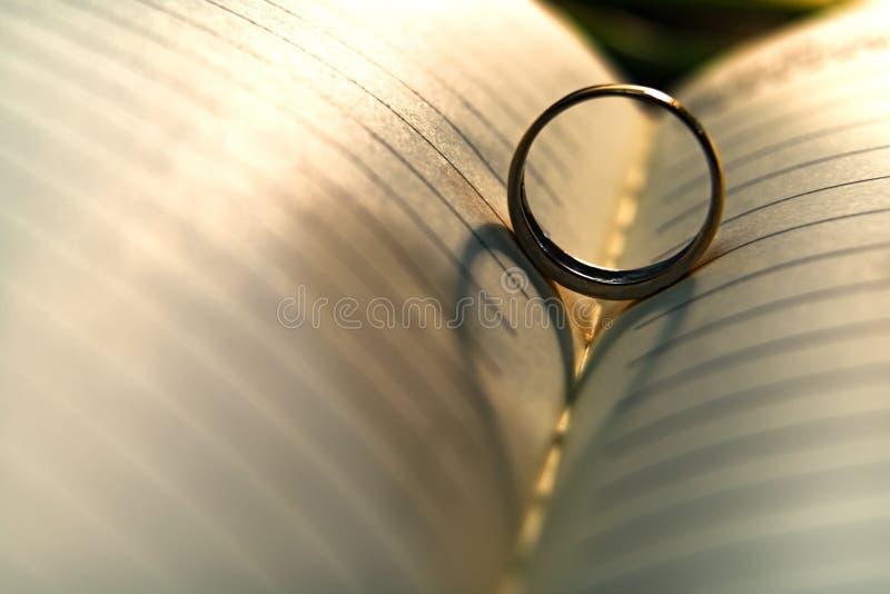 Abstrakter Hintergrund des Herzschattens des Eherings werfend auf der Buchseite stockfotografie