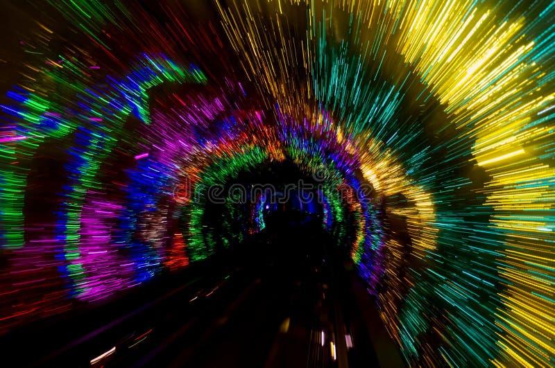 Abstrakter Hintergrund leuchtender Tunnel für Gold, Rot, Grün, Magenta und Blau im Dunkeln stockbilder
