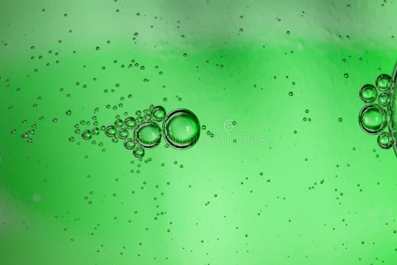 Abstrakter Hintergrund von den Blasen des Tafelwassers durch eine grüne Glasflasche stockbilder