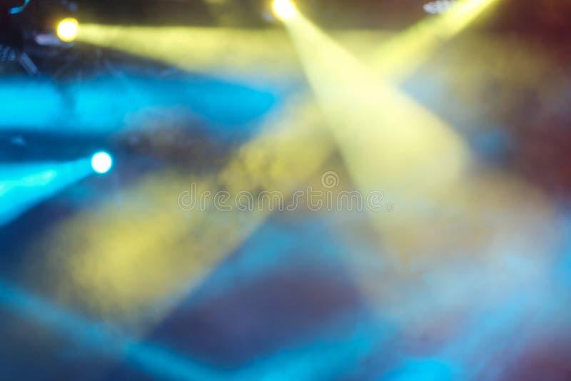 Abstrakter schöner Hintergrund von hellen mehrfarbigen Strahlen des Lichtes Gelbe und blaue Konzertlichter glänzen durch den Rauc stockfoto