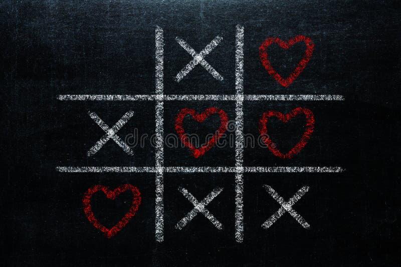 Abstrakter Tic Tac Toe Game Competition mit Herzform im Cer stockbilder