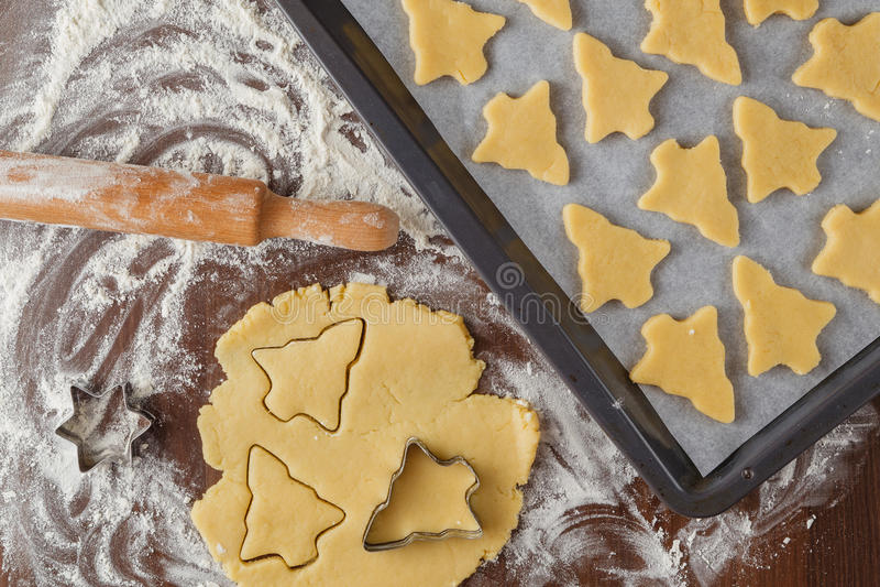 Abstrakter Weihnachtslebensmittelhintergrund mit Plätzchenformen und -mehl lizenzfreie stockbilder