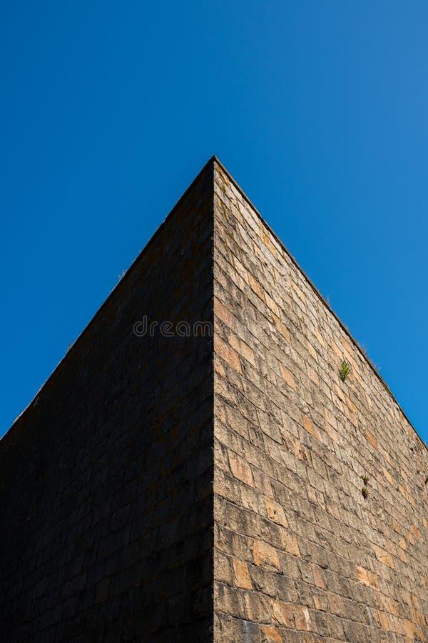 Abstraktes Architekturfreien Scharfer Winkel einer alten enormen Steinwandoberen ecke mit dunklem Schatten des Kontrastes und Son lizenzfreie stockfotografie