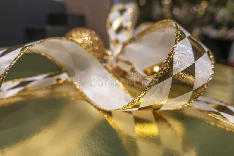 Abstraktes Bildweihnachtsgeschenk mit glänzenden Goldbändern und bokeh Hintergrund stockbild