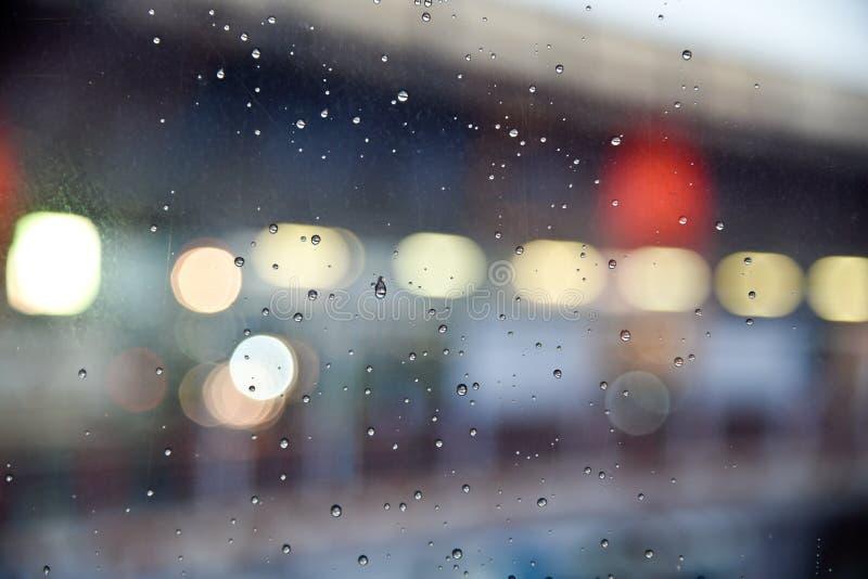 Abstraktes bokeh Licht mit Regenglashintergrund stockbild