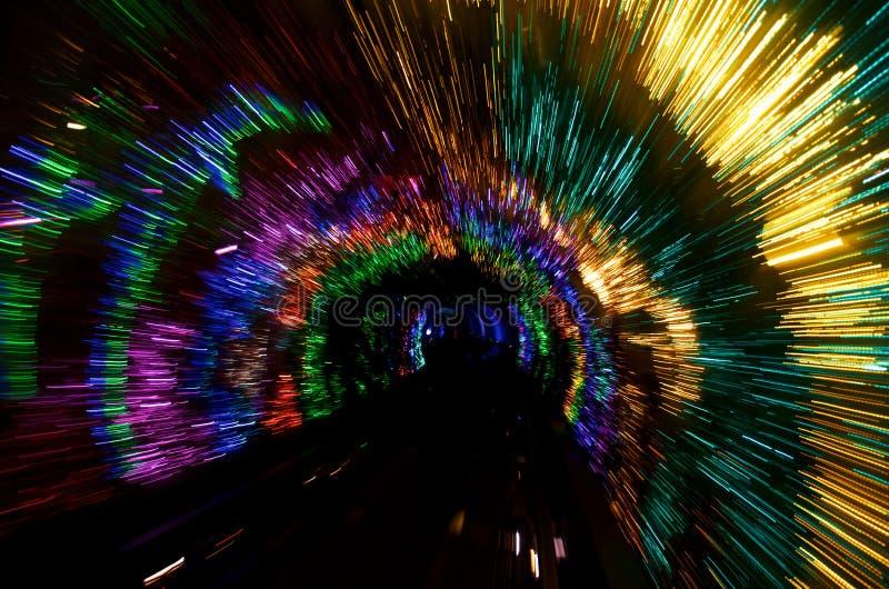 Abstraktes glühendes Gold, Rot, Grün, Magenta und Blaulichttunnel in der Dunkelheit lizenzfreies stockbild