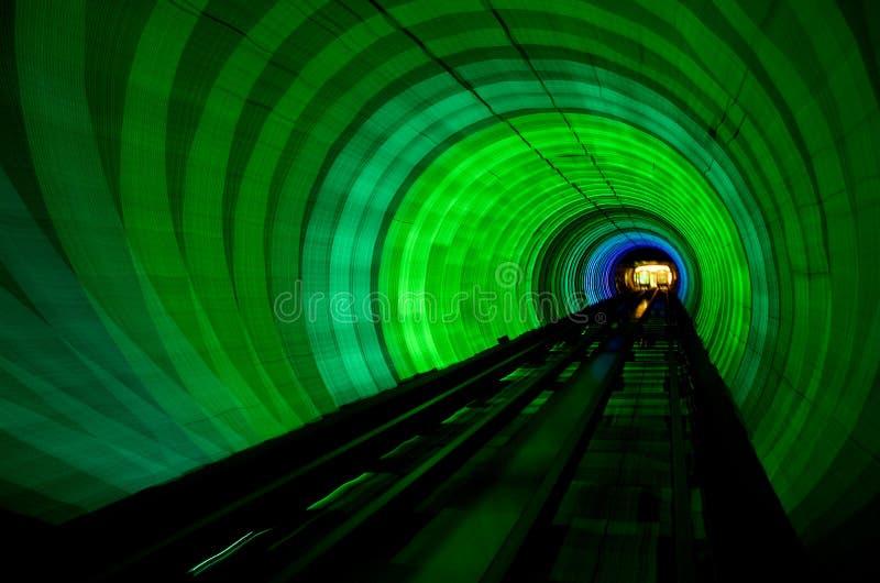 Abstraktes glühendes Gold, Rot, Grün, Magenta und Blaulichttunnel in der Dunkelheit lizenzfreie stockfotos